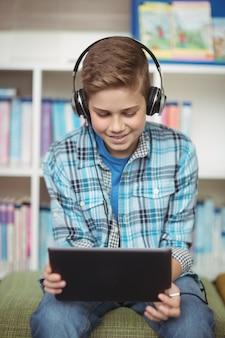 Aluno feliz ouvindo música enquanto usa o tablet digital na biblioteca