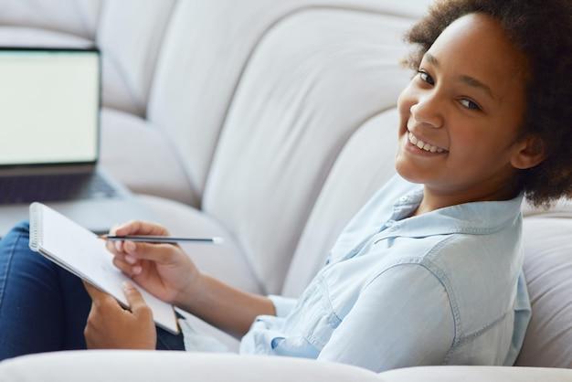 Aluno feliz sorrindo menina adolescente de raça mista olhando para a câmera enquanto faz o dever de casa sentada