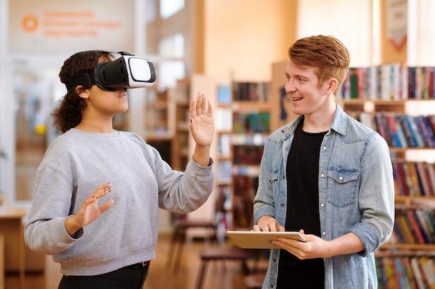 Aluno feliz usando o tablet enquanto interage com seu colega de classe com fone de ouvido vr na biblioteca
