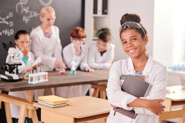 Aluno fofo e feliz da escola secundária em jaleco branco olhando para você com um sorriso nos colegas e na professora durante o trabalho de laboratório
