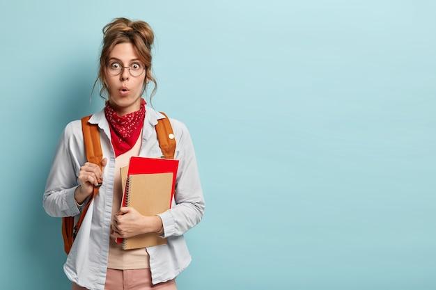 Aluno impressionado e estupefato frequenta cursos de línguas, segura blocos de notas, usa óculos, bandana vermelha e camisa