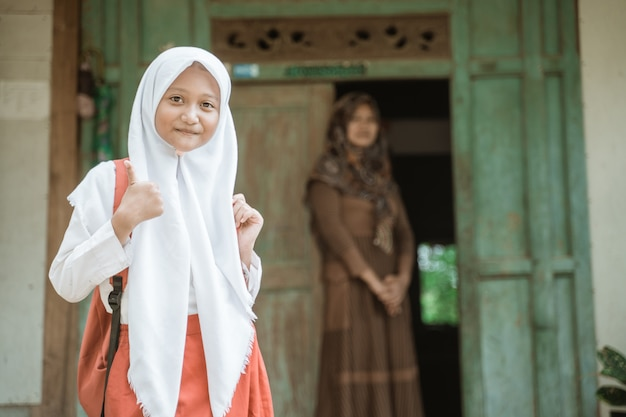 Aluno indonésio feliz se preparando para a escola pela manhã em pé na frente de sua casa