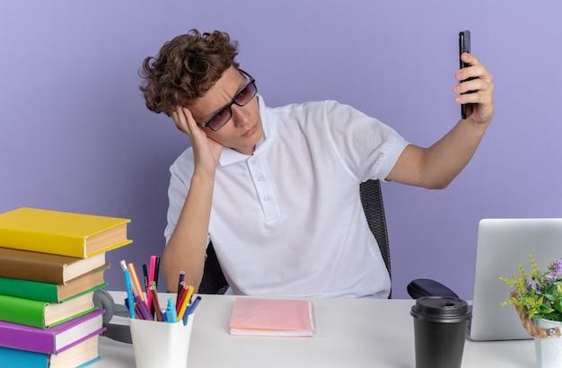 Aluno infeliz de camisa pólo branca de óculos, sentado à mesa com livros fazendo selfie usando smartphone parecendo insatisfeito com o fundo azul