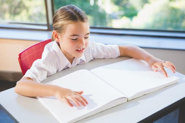 Aluno lendo livro braille em sala de aula