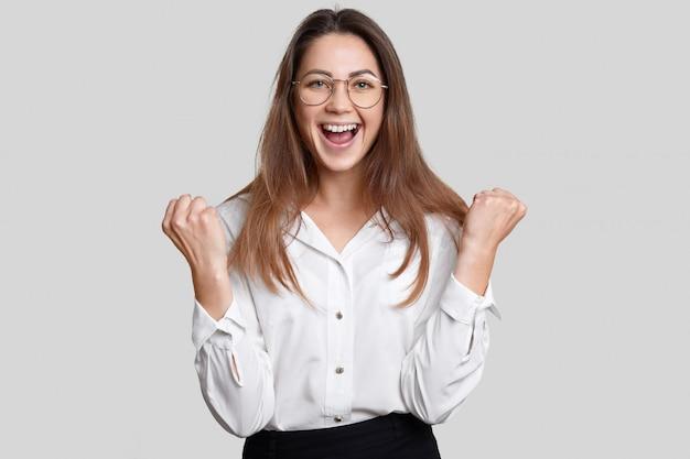 Aluno muito feliz usa roupas elegantes, aperta os punhos de felicidade, se alegra com sucesso no exame, sente-se como vencedor, posa sozinho contra um fundo branco. pessoas, sucesso, linguagem corporal