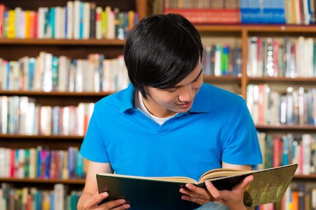 Aluno na biblioteca lendo livro