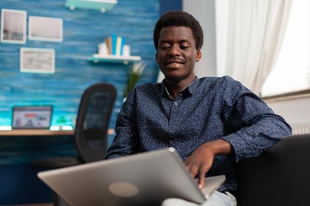 Aluno negro sentado no sofá da sala estudando gráfico administrativo