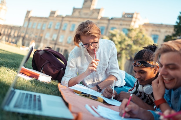 Aluno paciente. estudante pensativo segurando um lápis na boca, resolvendo problemas difíceis de matemática, deitado com os amigos na grama.