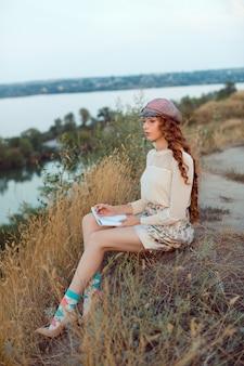 Aluno pensando e escrevendo notas. alegre garota feliz sentado escrevendo e lendo ao ar livre na natureza.