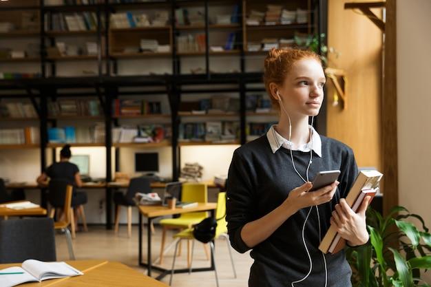 Aluno ruivo posando em um ambiente fechado na biblioteca segurando livros e ouvindo música com fones de ouvido usando o celular