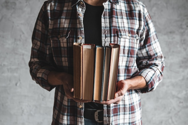 Aluno segurando na mão uma pilha de livros antigos. aprendizagem, sucesso, conhecimento