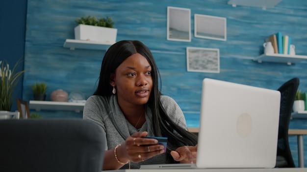 Aluno segurando um cartão de crédito nas mãos, fazendo compras online, pesquisando na loja, fácil pagamento usando um dispositivo digital