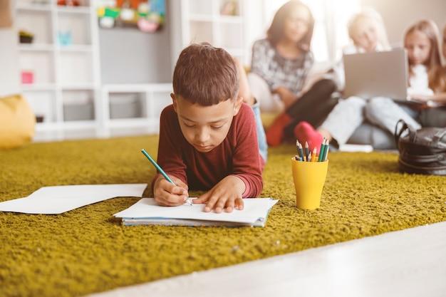 Aluno segurando um lápis e desenhando no papel no chão