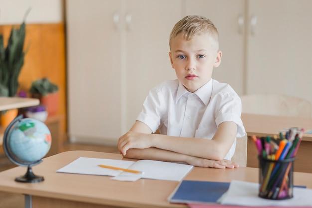 Aluno sentado com as mãos na mesa na sala de aula