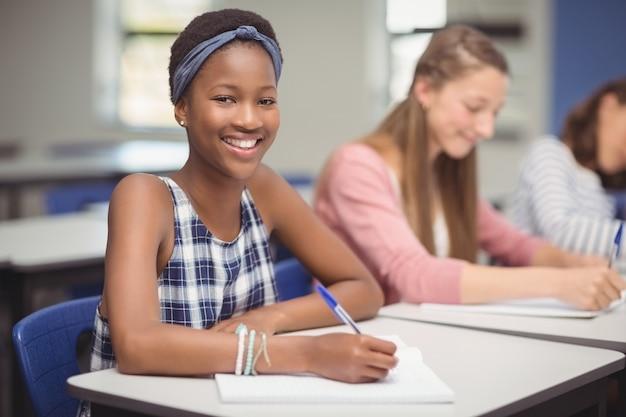 Aluno sentado na mesa da sala de aula