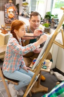 Aluno sentado perto do cavalete para colorir com o professor