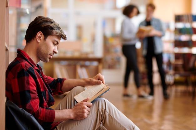 Aluno sério concentrado na leitura de um livro na biblioteca enquanto se prepara para o seminário ou exame