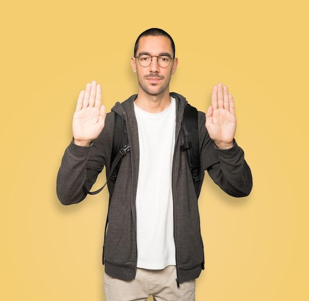 Aluno sério fazendo um gesto de parada com a palma da mão
