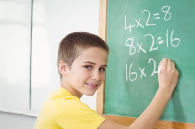 Aluno sorridente calculando no quadro-negro em uma sala de aula