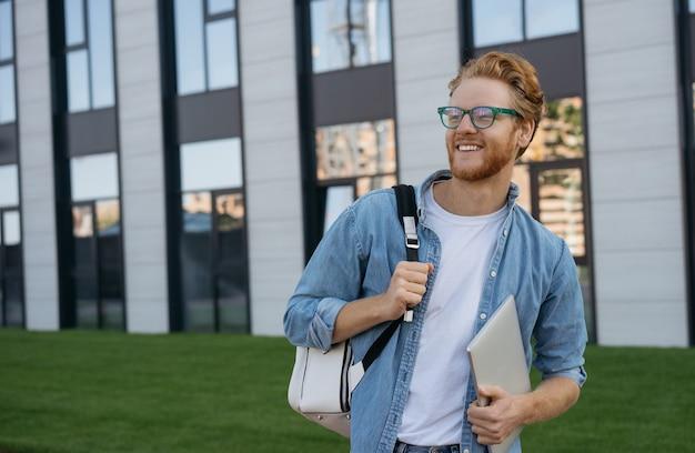 Aluno sorridente com mochila e laptop caminhando pelo campus da universidade