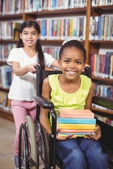 Aluno sorridente em cadeira de rodas segurando livros na biblioteca
