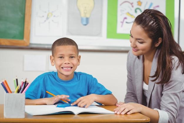 Aluno sorridente sendo ajudado pelo professor