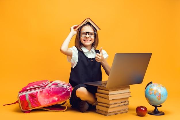 Aluno sorridente sentado atrás de uma pilha de livros e o pc segura o livro na cabeça mostra o polegar para cima educação infantil