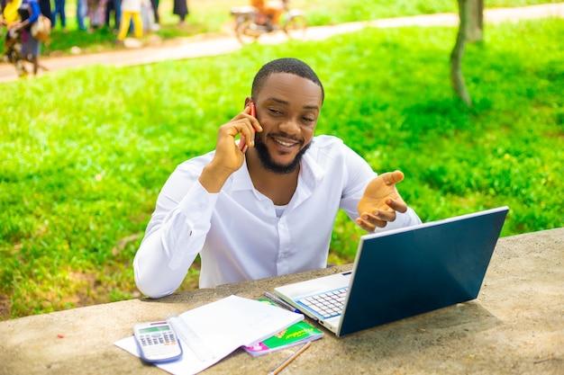 Aluno sorridente usando telefone celular ao ar livre