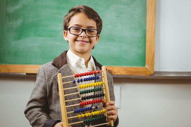 Aluno sorridente vestido como professor segurando ábaco