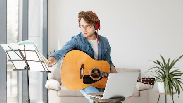 Aluno tocando guitarra e usando fones de ouvido tiro médio