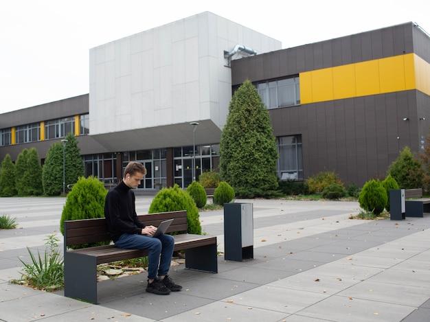 Aluno trabalha com um laptop em um parque perto da universidade