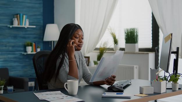 Aluno triste e chateado, interagindo com um colega explicando o curso de comunicação usando o telefone, sentado à mesa na sala de estar