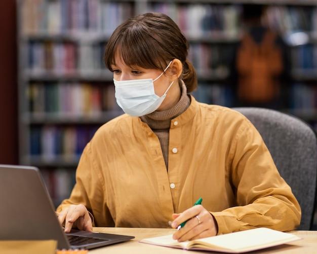 Aluno usando uma máscara facial na biblioteca