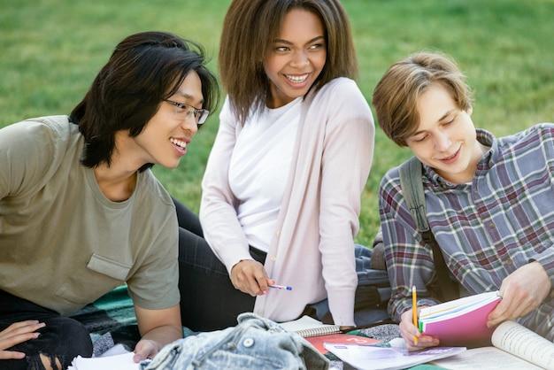 Alunos a estudar ao ar livre a sorrir