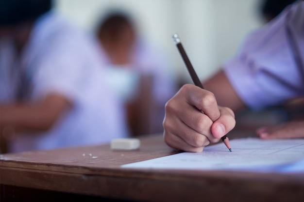 Alunos a fazer exame com estresse em sala de aula de escola.
