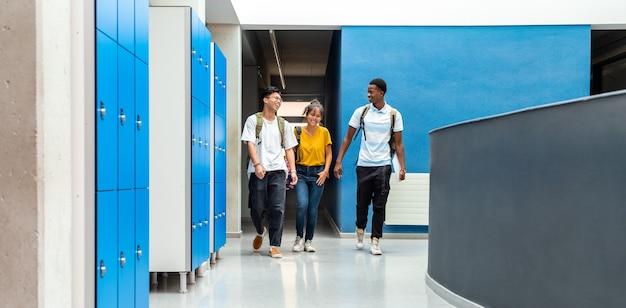 Alunos adolescentes do ensino médio caminhando no corredor da escola banner horizontal copiar espaço voltar para a escola