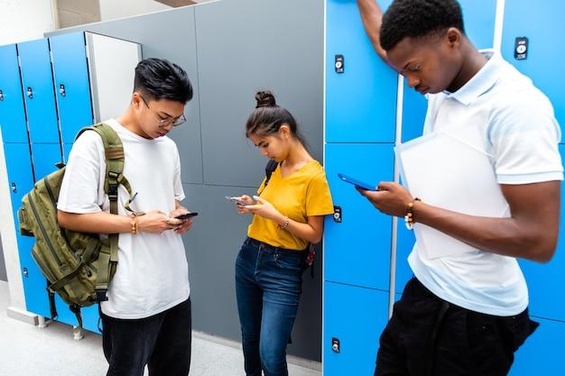 Alunos adolescentes multirraciais usando telefones celulares no corredor do ensino médio vício de adolescente nas redes sociais