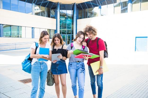 Alunos alegres com tablet e livros didáticos perto de prédio da universidade