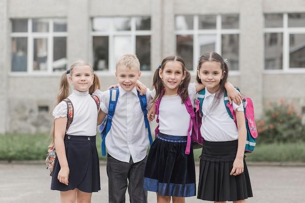 Alunos alegres em pé perto da escola