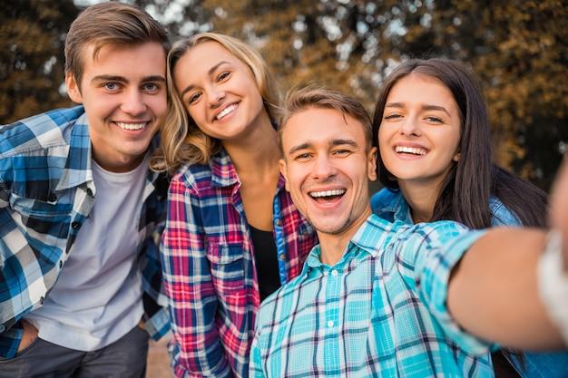 Alunos alegres tomando selfie no parque juntos.