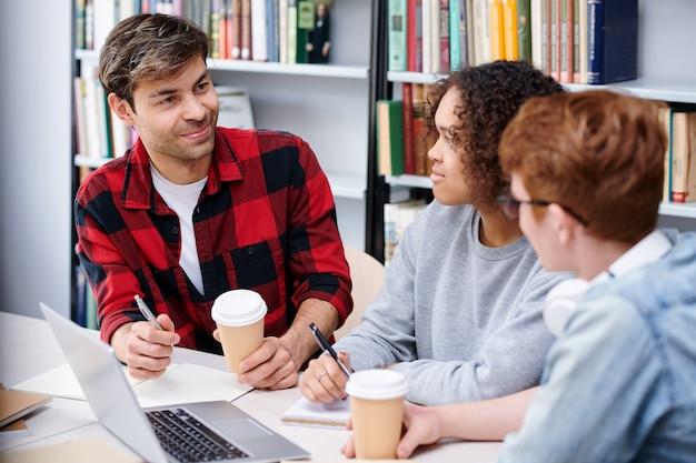 Alunos amigáveis com café, discutindo seus trabalhos escolares ou tarefas de casa enquanto estão sentados na biblioteca