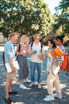Alunos animados juntos no pátio da universidade conversando e compartilhando suas impressões sobre a palestra