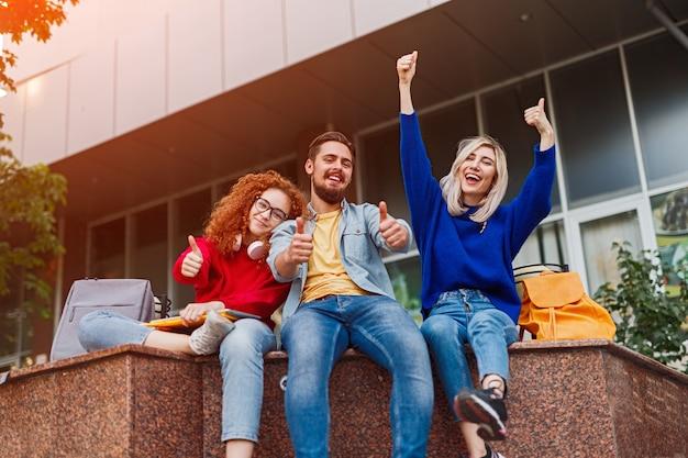 Alunos animados sentados do lado de fora do prédio da universidade