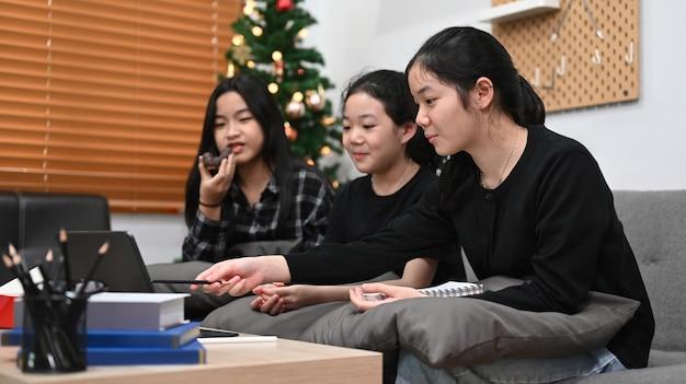 Alunos asiáticos aprendem online em casa juntos.