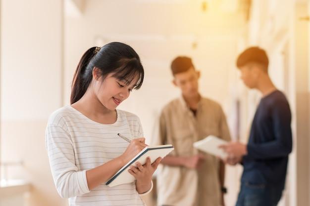 Alunos asiáticos confiantes menina bonito tomando nota com o sorriso na sala de aula exterior