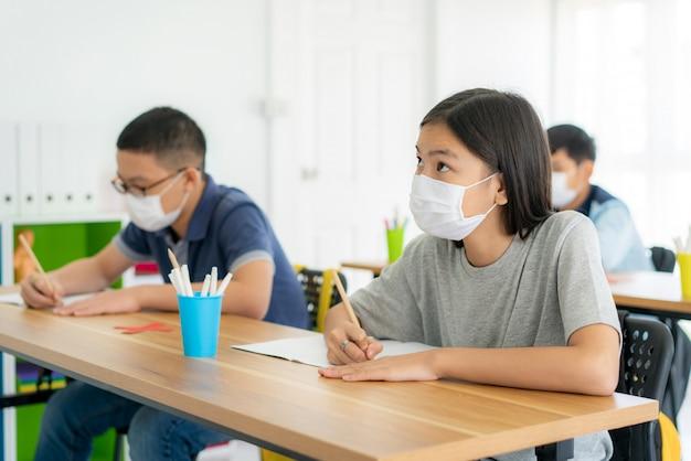 Alunos asiáticos da escola primária usando máscara de higiene