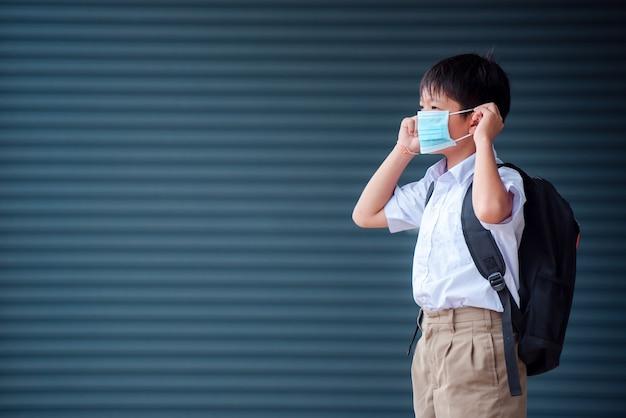 Alunos asiáticos do ensino fundamental use uma máscara médica para prevenir a infecção por coronavírus (covid 19) na escola.