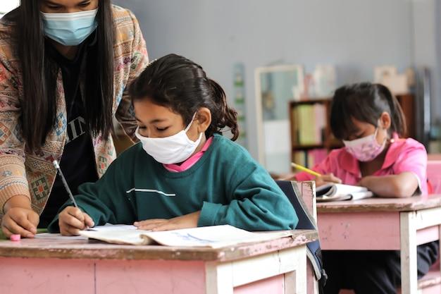 Alunos asiáticos estudando em sala de aula.