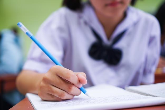 Alunos asiáticos segurando uma caneta em um uniforme escolar branco.