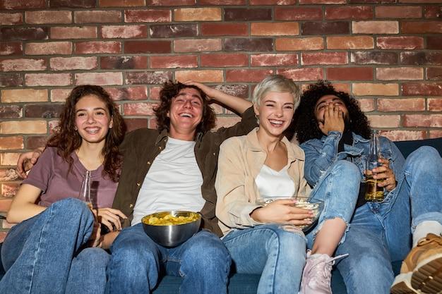 Alunos assistindo tv, programa de comédia ou filme, comendo lanches e bebendo bebidas, sentados no sofá aconchegante em casa, diversos rapazes e moças aproveitando o tempo livre, o fim de semana juntos